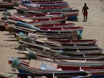 Ένα άτομο που περπατά στην παραλία Tarrafal εκτός από πολλές ζωηρόχρωμες μικρές ξύλινες βάρκες στοκ φωτογραφία με δικαίωμα ελεύθερης χρήσης