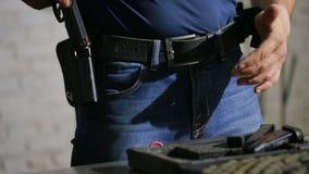 Ένα άτομο που προετοιμάζεται να πυροβολήσει ένα πυροβόλο όπλο Βάζει το πυροβόλο όπλο στην πιστολιοθήκη φιλμ μικρού μήκους