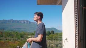 Ένα άτομο που στέκεται στο μπαλκόνι και που καπνίζει ένα τσιγάρο φιλμ μικρού μήκους