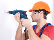 Ένα άτομο που τρυπά μια τρύπα στον τοίχο με τρυπάνι. Στοκ εικόνα με δικαίωμα ελεύθερης χρήσης