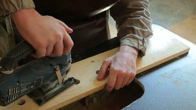 Ένα άτομο που τρυπά τα ξύλινα αεροπλάνα με τρυπάνι