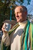 Ένα άτομο που τυλίγεται σε ένα κάλυμμα, με το φλιτζάνι του καφέ που στέκεται σε ένα Au Στοκ Φωτογραφίες