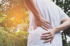 Ένα άτομο που υφίσταται τον πόνο στην πλάτη, το νωτιαίους τραυματισμό και το ζήτημα μυών Στοκ Φωτογραφία