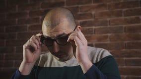 Ένα άτομο που φορά τα ειδικά προστατευτικά γυαλιά για τον υπολογιστή εργάζεται απόθεμα βίντεο