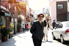 Ένα άτομο που φορά το μαύρο σακάκι δέρματος γυαλιών ηλίου που περπατά σε μια για τους πεζούς οδό στοκ εικόνα