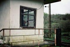 ένα άτομο που φρουρεί έναν σταθμό μετατροπής ραγών στο ορεινό μέρος της χώρας στο σταθμό του που κρυφοκοιτάζει από το παράθυρο στοκ φωτογραφίες