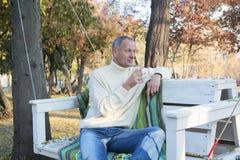 Ένα άτομο που χαλαρώνει με το φλιτζάνι του καφέ σε ένα πάρκο φθινοπώρου, που κάθεται στο s Στοκ Εικόνες