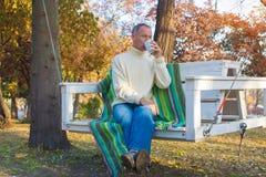 Ένα άτομο που χαλαρώνει, με το φλιτζάνι του καφέ σε ένα πάρκο φθινοπώρου, που κάθεται επάνω Στοκ Εικόνες