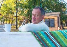 Ένα άτομο που χαλαρώνει, με το φλιτζάνι του καφέ σε ένα πάρκο φθινοπώρου, που εξετάζει Στοκ φωτογραφία με δικαίωμα ελεύθερης χρήσης