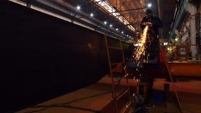 Ένα άτομο που χρησιμοποιεί μια αλέθοντας μηχανή στο σκοτάδι Λείανση της πλευράς της λεπτομέρειας Σπινθηρίσματα πυρκαγιάς φιλμ μικρού μήκους