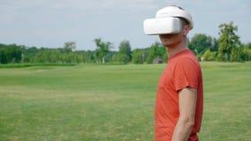 Ένα άτομο που χρησιμοποιεί μια κάσκα VR στο πάρκο και τις στροφές το κεφάλι του στη κάμερα απόθεμα βίντεο