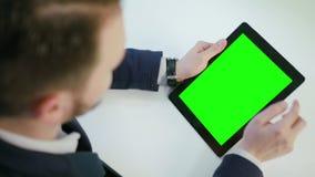 Ένα άτομο που χρησιμοποιεί μια ψηφιακή ταμπλέτα με μια πράσινη οθόνη Στοκ Φωτογραφία