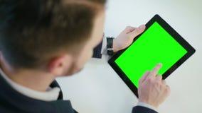 Ένα άτομο που χρησιμοποιεί μια ψηφιακή ταμπλέτα με μια πράσινη οθόνη Στοκ Εικόνες