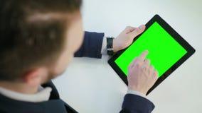 Ένα άτομο που χρησιμοποιεί μια ψηφιακή ταμπλέτα με μια πράσινη οθόνη Στοκ φωτογραφία με δικαίωμα ελεύθερης χρήσης