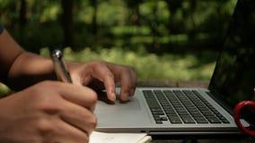 Ένα άτομο που χρησιμοποιεί στις σημειώσεις lap-top και γραψίματος στο πάρκο απόθεμα βίντεο
