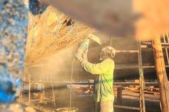 Ένα άτομο που χρησιμοποιεί το μύλο σε προετοιμασία για το αντι αποκρουστικό χρώμα που είναι app στοκ φωτογραφίες