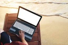 Ένα άτομο που χρησιμοποιεί το lap-top υπολογιστών στην ξύλινη καρέκλα σαλονιών sunbath στην παραλία το καλοκαίρι στο ηλιοβασίλεμα Στοκ φωτογραφίες με δικαίωμα ελεύθερης χρήσης