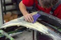 Ένα άτομο προετοιμάζει ένα στοιχείο σωμάτων αυτοκινήτων για τη ζωγραφική μετά από ένα ατύχημα στοκ εικόνες με δικαίωμα ελεύθερης χρήσης