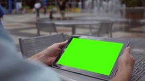 Ένα άτομο προσέχει μια πράσινη ταμπλέτα οθόνης στα στο κέντρο της πόλης χαρακτηριστικά γνωρίσματα νερού επιχειρησιακής περιοχής κ απόθεμα βίντεο