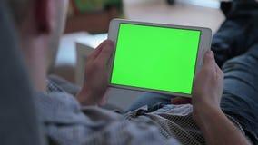 Ένα άτομο προσέχει την τηλεόραση κρατώντας και τρυπώντας σε μια συσκευή ταμπλετών απόθεμα βίντεο