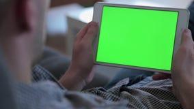 Ένα άτομο προσέχει την τηλεόραση κρατώντας και τρυπώντας σε μια συσκευή ταμπλετών φιλμ μικρού μήκους