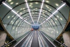 Ένα άτομο προσωπικού καθαριότητας στο πορτοκαλί παλτό στην κυλιόμενη σκάλα στο σύγχρονο, φουτουριστικό σταθμό μετρό αρχιτεκτονική στοκ εικόνες