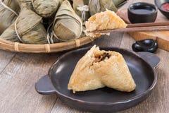 Ένα άτομο πρόκειται να φάει την μπουλέττα zongzi ή ρυζιού στο φεστιβάλ βαρκών δράκων Στοκ Εικόνα