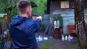 Ένα άτομο πυροβολεί ένα πυροβόλο όπλο στη μελιτζάνα που γεμίζουν με το νερό φιλμ μικρού μήκους