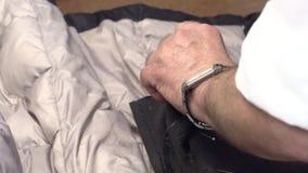 Ένα άτομο ράβει τα ενδύματα σε ένα χέρι φιλμ μικρού μήκους
