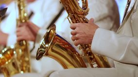 Ένα άτομο σε ένα άσπρο κοστούμι παίζει ένα saxophone σε μια ορχήστρα τζαζ Κινηματογράφηση σε πρώτο πλάνο Μικρό DOF απόθεμα βίντεο
