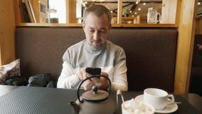 Ένα άτομο σε έναν καφέ με ένα τηλέφωνο στα χέρια απόθεμα βίντεο