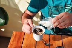 Ένα άτομο σε έναν καφέ χύνει την κρέμα σε ένα φλιτζάνι του καφέ το πρωί Πρόγευμα στοκ εικόνες