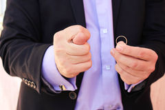 Ένα άτομο σε ένα επιχειρησιακό κοστούμι παρουσιάζει figo, αφ' ετέρου παρουσιάζει γαμήλιο δαχτυλίδι Η έννοια του ατόμου δεν θέλει  Στοκ φωτογραφία με δικαίωμα ελεύθερης χρήσης