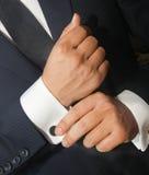 Ένα άτομο σε ένα μαύρο κοστούμι ισιώνει τα μανικετόκουμπά του Στοκ Φωτογραφία