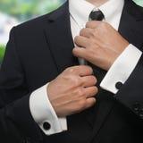 Ένα άτομο σε ένα μαύρο κοστούμι ισιώνει το δεσμό του Στοκ Φωτογραφία