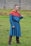ένα άτομο σε ένα μεσαιωνικό φόρεμα με δύο που δίνεται το ξίφος Στοκ φωτογραφίες με δικαίωμα ελεύθερης χρήσης