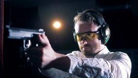 Ένα άτομο σε ένα δωμάτιο πυροβολισμού στοχεύει με ένα πυροβόλο όπλο στα χέρια του φιλμ μικρού μήκους