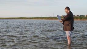 Ένα άτομο σε ένα επιχειρησιακό κοστούμι και τα σώβρακα στέκεται με ένα lap-top στα χέρια του και γόνατο-βαθιά στο νερό φιλμ μικρού μήκους