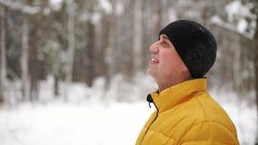 Ένα άτομο σε ένα κίτρινο σακάκι εξετάζει το χιόνι το χειμώνα στα ξύλα και χαμογελά σε σε αργή κίνηση φιλμ μικρού μήκους