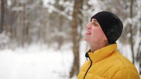 Ένα άτομο σε ένα κίτρινο σακάκι εξετάζει το χιόνι το χειμώνα στα ξύλα και χαμογελά σε σε αργή κίνηση απόθεμα βίντεο