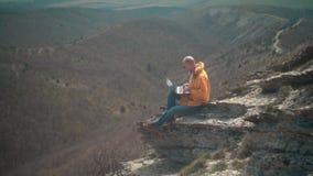 Ένα άτομο σε ένα κίτρινο σακάκι, το τζιν παντελόνι και τα γυαλιά κάθεται στην άκρη ενός απότομου βράχου και εργάζεται σε ένα lap- απόθεμα βίντεο