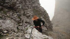 Ένα άτομο σε ένα καπέλο αναρριχείται επάνω στο βουνό σε ένα σχοινί απόθεμα βίντεο