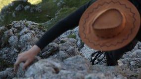 Ένα άτομο σε ένα καπέλο αναρριχείται στο βουνό απόθεμα βίντεο