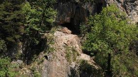 Ένα άτομο σε ένα καπέλο κάθεται στην άκρη ενός απότομου βράχου στη θέση και meditates τη μελέτη λωτού του απείρου : φιλμ μικρού μήκους