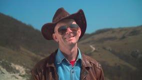 Ένα άτομο σε ένα καπέλο κάουμποϋ, σακάκι δέρματος, γυαλιά Το άτομο εξετάζει το πλαίσιο και χαμογελά φιλμ μικρού μήκους