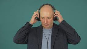 Ένα άτομο σε ένα κοστούμι βάζει στα ακουστικά Όμορφο ενήλικο άτομο που βάζει στα ακουστικά φιλμ μικρού μήκους