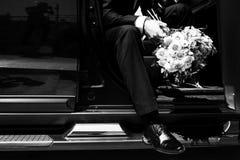 Ένα άτομο σε ένα κοστούμι κρατά μια γαμήλια ανθοδέσμη στενού επάνω λουλουδιών στοκ εικόνες