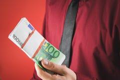 ένα άτομο σε ένα κόκκινο πουκάμισο με μια κάρτα κρατά στο χέρι του ένα wad των λογαριασμών σε ένα κόκκινο υπόβαθρο στοκ εικόνες
