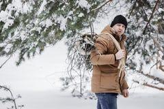 Ένα άτομο σε ένα κόκκινο σακάκι με brushwood και ένα σχοινί στο χειμερινό δασικό άτομο συλλέγει το καυσόξυλο Στοκ Φωτογραφίες