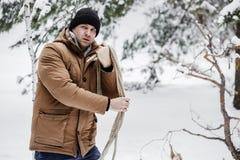 Ένα άτομο σε ένα κόκκινο σακάκι με brushwood και ένα σχοινί στο χειμερινό δασικό άτομο συλλέγει το καυσόξυλο Στοκ Εικόνες